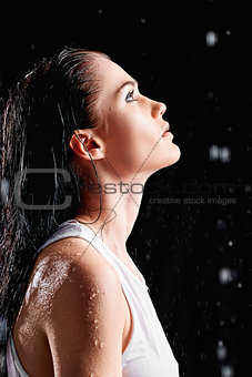 Portrait of beautiful young woman in water studio. Profile view