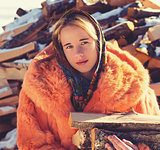 Teenage girl in red fur coat with firewood.