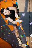 Young man practicing rock-climbing in climbing gym indoors