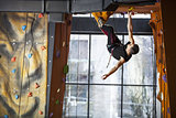 Young man practicing rock-climbing on a rock wall indoors