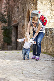 Cute baby boy makes his first steps with help of his mother. Young woman carrying touristic backpack