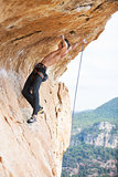 Young man clipping rope while clinging to cliff under ledge, challenging part of route
