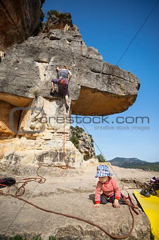 Toddler boy playing at foot of mountain while his mother climbing at the background. The boy is tied in to the rope.