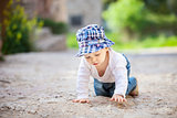 Cute little boy crawling on stone paved sidewalk