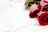 roses and a blank sheet of paper on a marble surface