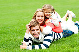 Smiling family of three piled on top of each other