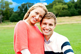 Young couple outdoors sitting on green grass