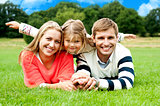 Couple lying in park with their daughter on top