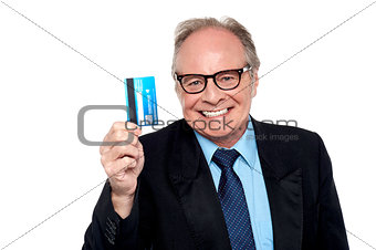 Old man wearing eyeglasses holding up a cash card