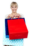 Woman holding shopping bags in her outstretched arms