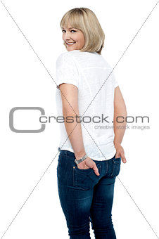 Smartly dressed woman with hands in back pocket of jeans