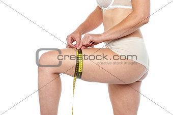 Fit woman in lingeries measuring her thighs