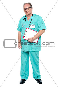 Portrait of grim faced doctor holding a clipboard