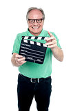 Bespectacled elderly man holding a clapperboard