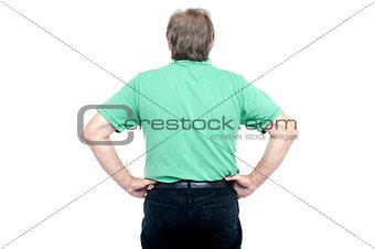 Back pose of elderly guy with hands on his waist