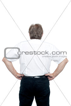 Back pose of a senior man standing with hands on his waist