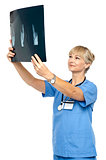 Orthopedic surgeon holding up x-ray to analyze