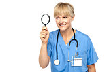 Pretty physician looking through magnifying glass