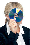 Corporate lady looking through compact disc hole