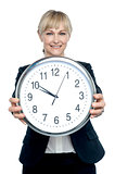 Business executive displaying big wall clock