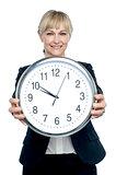 Business executive displaying big wall clock