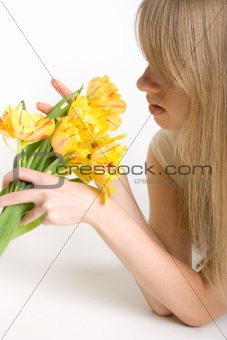 Sexy girl with bright yellow tulips in hands