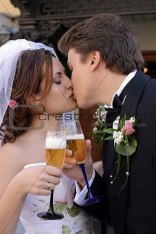 Bride and groom kissing and toasting each other