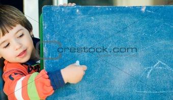 boy painting in a blackboard