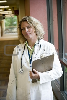 female medical professional with clipboard in hallway