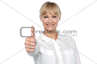Blonde woman in formal attire showing thumbs up gesture