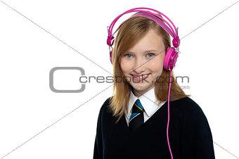 Cute teenager listening to music through headphones