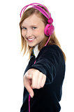 Pretty musical girl enjoying music and pointing at you