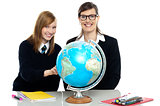 Teacher and student viewing globe in geography classroom