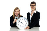 Pretty student holding clock with her teacher