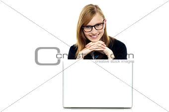 Charming schoolgirl sitting with her laptop open