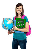 Smiling female student holding a calculator and globe