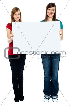 Pair of good looking women holding whiteboard