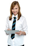 Cheerful student in school attire using tablet pc