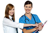 Attractive girl pointing at the doctors case sheet