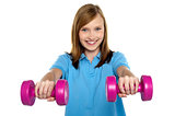 Adorable teen holding dumbbells in her outstretched arms
