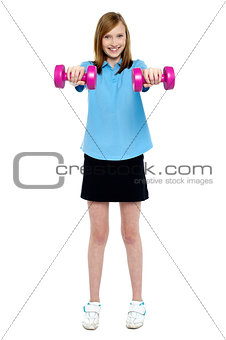 Slim girl striking a pose with dumbbells. Lifting weights