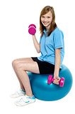 Pretty teen seated on a blue pilate ball doing dumbbells