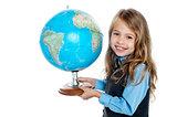 Beautiful school going kid holding globe