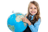 Pretty school child holding globe and pointing