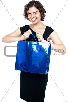 Cute young lady with a blue shopping bag