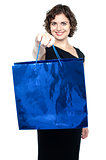 Woman offering you bright blue shopping bag