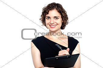Charming woman writing notes on clipboard