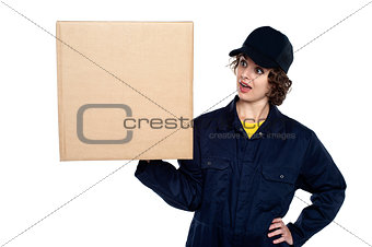 Amazed young lady holding a sealed carton