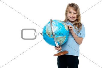 Smart young girl showing her country on a globe
