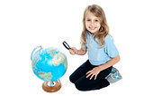 Girl watching globe through magnifying glass